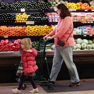 Customers shop in the produce section at the Whole Foods grocery story in Ann Arbor, Michigan