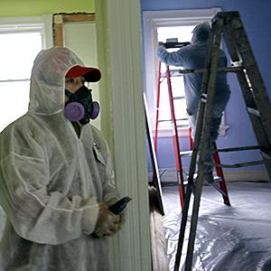 Contractors Luis Benitez and Jose Diaz clean up lead paint in a contaminated building in Providence, R.I. on Feb. 23, 2006 (© Chitose Suzuki/AP Photo)
