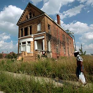 A man walks past a vacant, boarded-up home near downtown Detroit, Michigan on July 19, 2013 (© Rebecca Cook/Newscom/Reuters)
