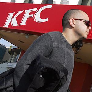A man walks by a KFC restaurant with no Colonel Sanders in the sign. (© David Silverman/Getty Images)