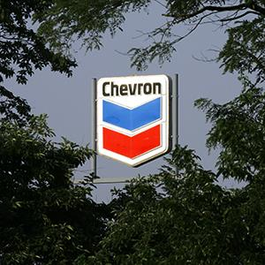 A sign for a Chevron gasoline station is seen through trees in La Grange, Ky.,
