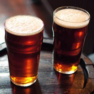 Two pints of beer on barrel (© Adermark Media/Flickr/Getty Images)