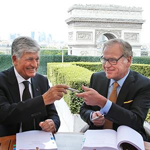 Maurice Levy, left, Chief Executive of French advertising group Publicis, and John Wren, head of Omnicom Group exchange a pencil during a joint signature prior to a news conference in Paris, France, Sunday, July 28, 2013 (© Francois Mori/AP)