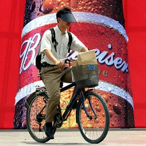 File photo of a cyclist riding past a Budweiser billboard in Beijing (© STR/AP)
