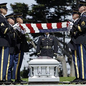 Members of US Army Honor Guard hold a flag over the casket of John P. Bonnassiolle at a funeral service with full military honors in Colma, Calif. on Aug. 10, 2010 (© Jeff Chiu/AP Photo)
