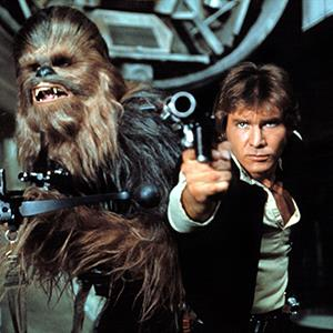 Movie still of Harrison Ford as Han Solo and Chewbacca in Star Wars: Episode IV (© Lucasfilm Ltd./Courtesy Everett Collection)