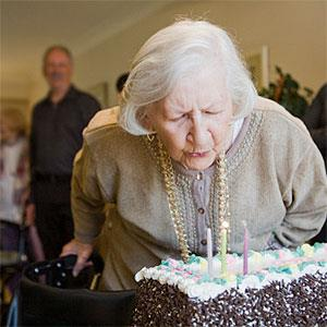 Senior woman blows out candles on birthday cake (© Jaime Kowal, Photodisc, Getty Images)