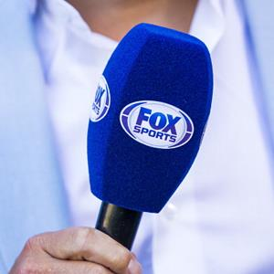 A Fox Sports commentator holds a microphone during a soccer match in The Hague, Netherlands, on August 3, 2013 (© VI Images via Getty Images)