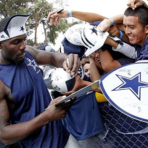 Dallas Cowboys wide receiver Dez Bryant signs for fans after the Cowboys Blue-White scrimmage on July 28, 2013 (© Paul Moseley/Fort Worth Star-Telegram/MCT via Getty Images)