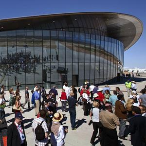 Guests stand outside the Spaceport America hangar in Upham, NM, on Oct. 17, 2011 (© Matt York/AP)