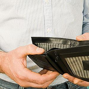 Man holding empty wallet (© CharlesSturge.com, Image Source, Getty Images)