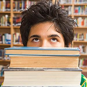 Teenage boy behind a stack of books (© Jupiterimages, Brand X Pictures, Getty Images)
