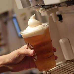 Employees pull frozen froth heads onto cups of Kirin draft beer for their
