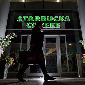 A pedestrian walks past a Starbucks Corp. store in Toronto, Ontario, Canada, on Tuesday, July 23, 2013. (© Brent Lewin/Bloomberg via Getty Images)