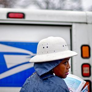 U.S. Postal Service letter carrier of 12 years, Jamesa Euler, delivers mail in the rain in Atlanta, on Feb. 17, 2013 (© David Goldman/AP)