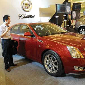 A man looks at a Cadillac as the US manufactured car is promoted at a shopping mall in Beijing (© MARK RALSTON/AFP/Getty Images)