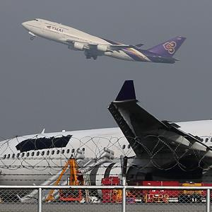A plane takes off over a damaged Thai Airways Airbus A330-300 at Suvarnabhumi International Airport in Bangkok, on Monday (© Apichart Weerawong/AP)