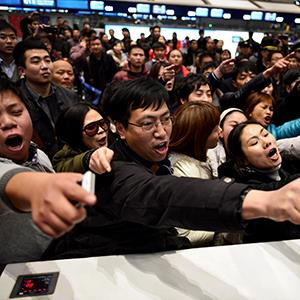 Stranded travelers arguing at an airline counter at Changshui International Airport after massive flight delays stranded thousands of people on January 4, 2013 (© STR/AFP/Getty Images)