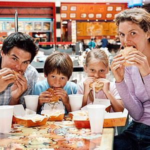 Family eating fast-food burgers (© Bananastock/Jupiterimages)