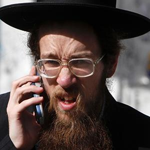 An ultra Orthodox Jewish man speaks on his cellular phone along a street in Bnei Brak, near Tel Aviv, May 3, 2011 (© Nir Elias/Newscom/Reuters)