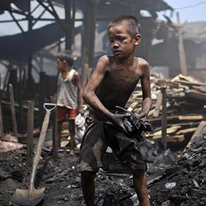 Filipino child laborers work in the charcoal dump of Port area district on July 9, 2012 in Manila, Philippines (© Dondi Tawatao/Getty Images)