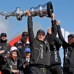 Oracle CEO Larry Ellison holds up the Auld Mug on podium as the crew celebrates after Oracle Team USA won the America's Cup sailing event over Emirates Team New Zealand on Wednesday, Sept. 25, 2013, in San Francisco (© Marcio Jose Sanchez/AP)