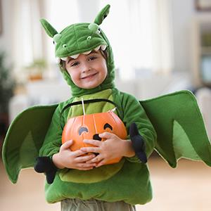A boy in a Halloween dragon costume holding candy (©KidStock/Getty Images)