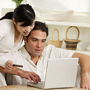 Couple with computer and credit card © Fuse, Getty Images
