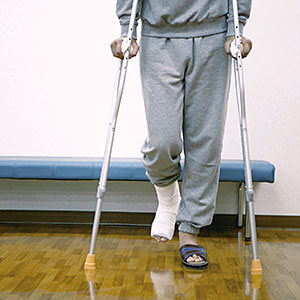 Man with cast on leg using crutches in exam room © DAJ, amana images, Getty Images