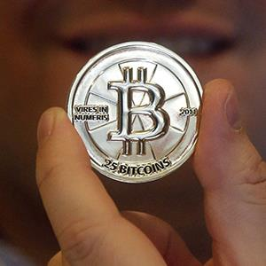Mike Caldwell, a 35-year-old software engineer, holds a 25 Bitcoin token at his shop in Sandy, Utah on April 3, 2013 (© Rick Bowmer/AP Photo)