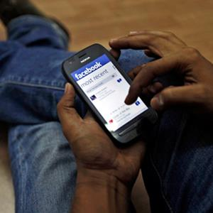 A man surfs the Facebook site on his mobile phone in Mumbai, India, 2012 &#169; Rajanish Kakade/AP&#xA;