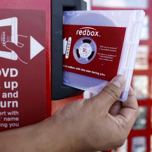 A rental DVD is dispensed from a Redbox &#169; Damian Dovarganes/AP Photo