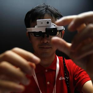 A staff member of NTT DoCoMo Inc wears a head-mounted 'intelligent glass' in Chiba, Japan, on September 30, 2013 (© Yuya Shino/Reuters)