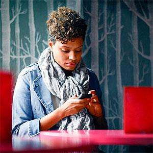 Woman Sitting in a Cafe Texting copyright Stephen Morris, Vetta, Getty Images