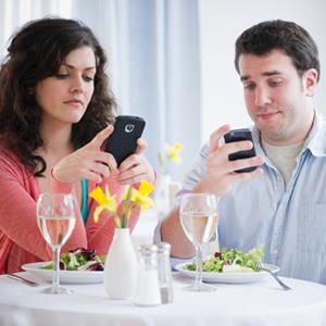 Couple using smartphones while in a restaurant (copyright Jamie Grill/Getty Images)