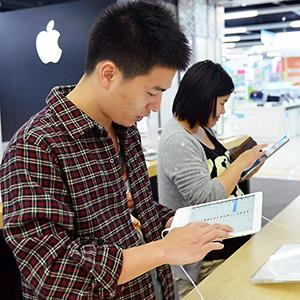 Customers try out an Apple iPad Air © Imaginechina/Corbis