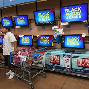 Shoppers browse TVs at a Walmart pre-Black Friday event in 2012 © Damian Dovarganes/AP