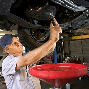Image: Man changing oil -- Ron Chapple, Getty Images