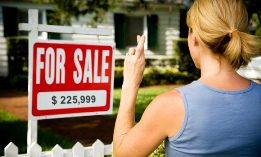 Woman in front of sale sign with fingers crossed (© SuperStock)