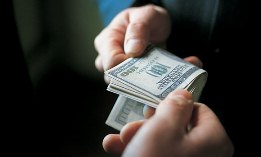 Hands exchanging stack of hundred-dollar bills ( James Lauritz/Getty Images)