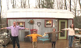 Video still of family with tiny house ( Andersoncooper.com Via YouTube, http://aka.ms/uqp5rg)