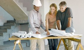 Construction foreman explaining blueprints to couple (© Robert Daly/Getty Images)