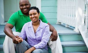 Couple sitting on front porch of house (&#169; Corbis)