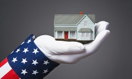Uncle Sam holding a model home (© Peter Gridley/Getty Images)