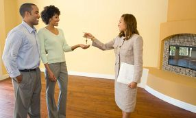 Real-estate agent handing keys to homebuyers. © Mark Scott/Getty Images