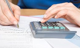 Man writing check, calculator, bills (© Dana Hoff/Getty Images)