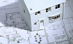Model house on blueprints (© Image Source/Getty Images)