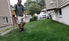 Joseph Perazzo, owner of Grass is Greener Lawn Painting, demonstrates how he spays lawns at a house on the Staten Island borough of New York.