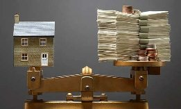 Model house and money on scale. © SuperStock