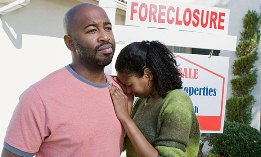Couple in front of foreclosed house (© moodboard/Alamy)